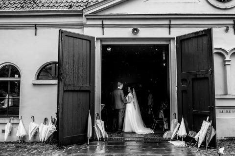 La novia y el novio se cubren de la lluvia y están rodeados de paraguas. El fotógrafo de bodas Indra Simons de Overijssel, Países Bajos, capturó esta gran imagen en blanco y negro en la recepción.