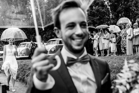 El fotógrafo de bodas Philippe Swiggers de Vlaams Brabant, Bélgica hizo esta imagen de la novia y el novio con paraguas bajo la lluvia en su boda.