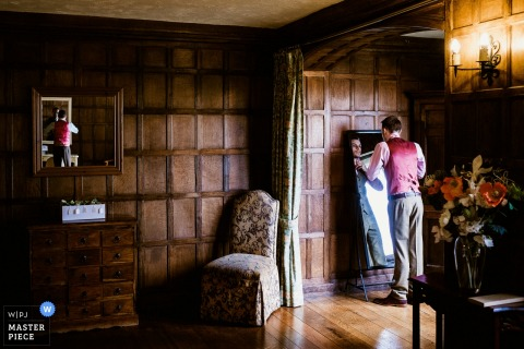 Kent wedding photographer captures this groom straightening his bow tie in a paneled room