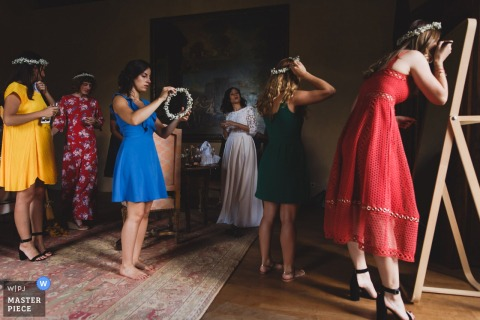 Bridesmaids dressed differently with the exception of their floral crown, finish primping in this image captured by a Paris wedding photographer