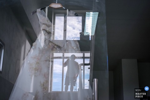 Bangkok wedding photographer captured this image of a grooms silhouette on a stairway while his brides wedding dress is reflected into the image