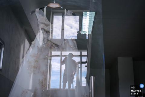 Fotograf ślubny Bangkoku uchwycił ten obraz sylwetki stajennych na schodach, podczas gdy jego suknia ślubna narzeczonych odbija się w obrazie