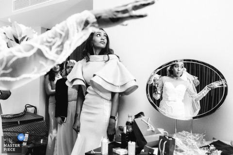 This black and white photo of the bride looking into a mirror while her bridesmaids wait nearby was captured by a London wedding photographer