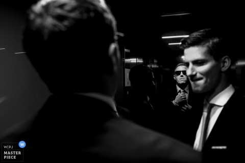 North Rhine-Westphalia wedding photographer captured this black and white photo of a groom smugly appreciating his reflection in the mirror