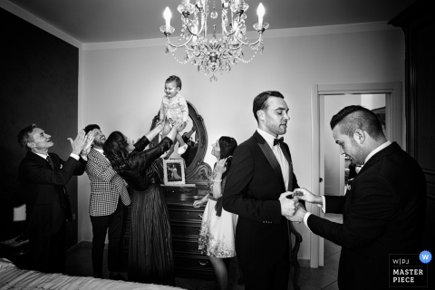 This black and white photo of a baby being entertained by a group of people while her father finishes getting ready nearby was captured by a Reggio Calabria wedding photographer