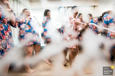 This photo of a bride holding a spraying bottle of champagne while her bridesmaids watch nearby in matching blue floral robes was captured by an Atlantic City wedding photographer
