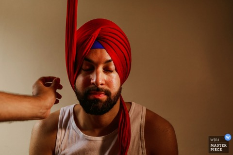 London wedding photographer captured this image of the groom getting assistance in putting on his turban before the wedding ceremony