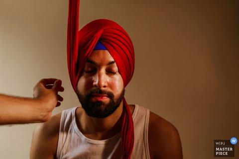 Der Londoner Hochzeitsfotograf hat dieses Bild des Bräutigams aufgenommen, der vor der Hochzeitszeremonie Unterstützung beim Anziehen seines Turban erhält