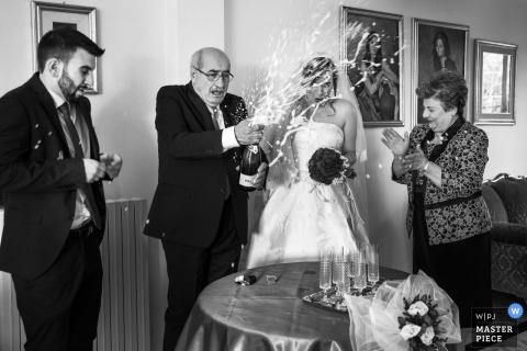 Cosenza-huwelijksfotograaf ving dit beeld van de bruiden verraste vader die een bespuitende fles champagne houden terwijl zijn vrouw en de bruidegom zich dichtbij bevinden