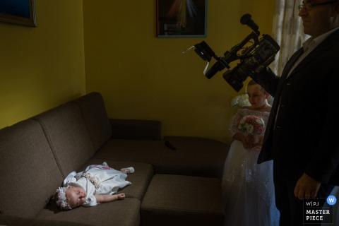 Trouwfotograaf uit Calabrië veroverde deze videograaf hard op het werk om een opname van een slapend kind te krijgen voordat de ceremonie begint