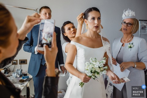De het huwelijksprofiefoto van heilige-Petersburg ving deze foto van een bruid die haar haar aanpast vóór de ceremonie aangezien haar mamma en vriendenhorloge met zorg