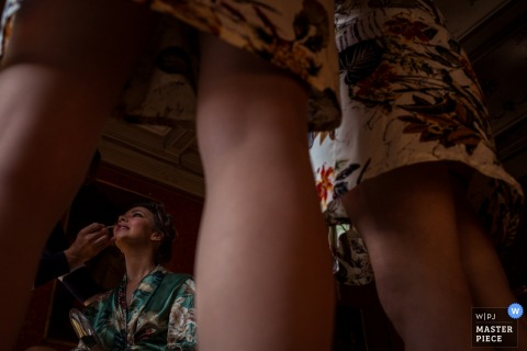 Florence wedding photographer captured this image at ground level looking up through bridesmaids legs at a bride getting the final touches put on her lipstick