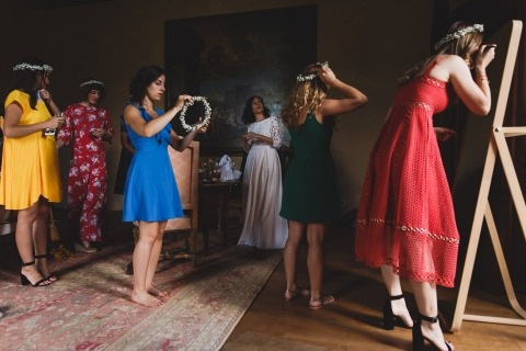 WPJA Wedding Photo by Annie Gozard of France of bridesmaids putting flowers in their hair and applying makeup.