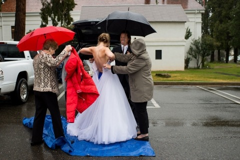 Wedding Photo by Matt Theilen of California of a bride getting dressed outside in the rain with umbrellas.
