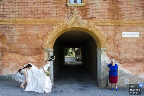 Rome wedding photographer captured this photo of a bride peering into a tunnel while a bridesmaid protects her dress from the ground