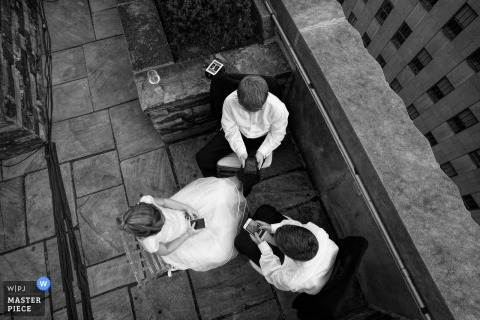 Bronx wedding photographer captured this overhead shot of a group of wedding guests sitting in a circle and texting on their phones