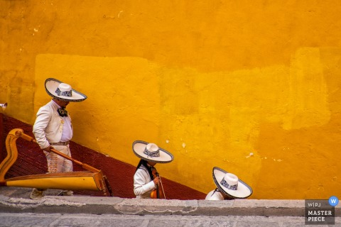 This image of a mariachi band making it's way down a flight of stairs in front of a bright yellow wall was captured by a San Diego wedding photographer