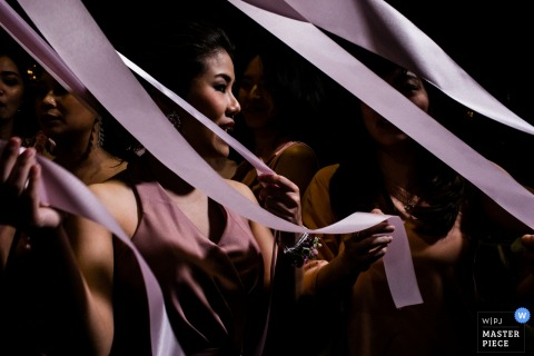 Nonthaburi wedding photographer captured this image of the bridesmaids holding on to pink ribbon as they get ready for the reception