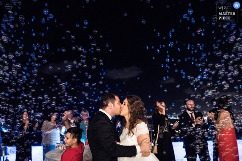 Caserta wedding photographer captured this photo of the bride and groom kissing under a night sky filled with bubbles