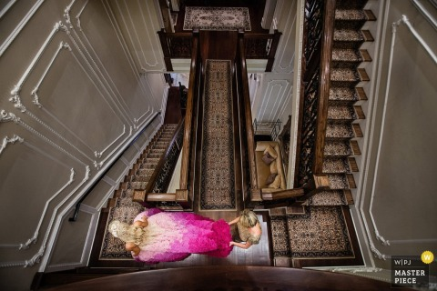 This overhead photo of a bride in a pink dress traveling down numerous flights of stairs was captured from above by New Jersey wedding photographer