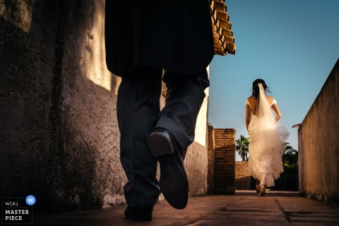 Barcelona wedding photographer captured this ground level image of a bride walking down a path while the groom follows close behind