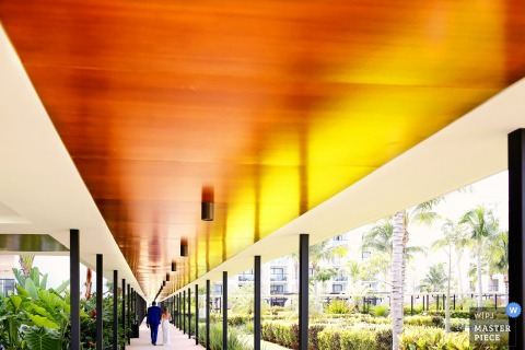 Playa del Carmen wedding photographer created this image of a bride and groom walking down a long outdoor covered sidewalk while tropical foliage line either side