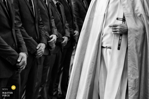 Lake Tahoe wedding photographer captured this black and white detail shot of a line of groomsmen hands while the priest stands across from them
