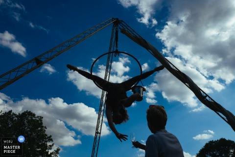London wedding photographer captured this photo of an aerial performer hanging upside down under a blue sky