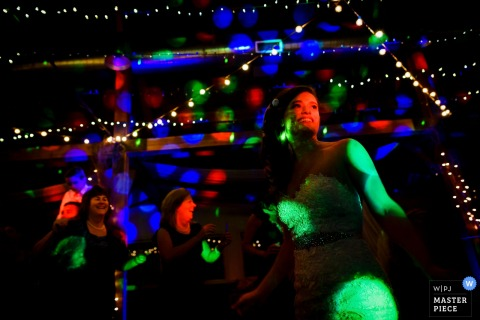 Burlington wedding photographer captured this image of the bride dancing in a dark room while being lit up by blue, green, and red lights