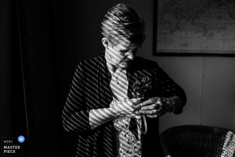 New South Wales wedding photographer captured this black and white image of the grooms mother attaching her boutonniere as the light shining through the blinds casts a pattern on the room