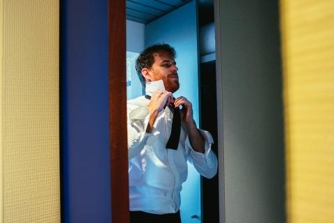 El novio poniéndose su papillon. Juego de colores opuestos y líneas verticales. Foto de Roma, con sede en Italia Alessandro Avenali.
