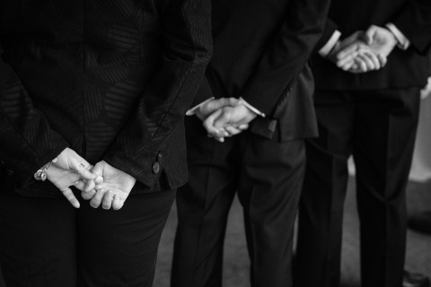 El fotógrafo de bodas de Colorado Kent Meireis se centró en las manos de los padrinos de boda durante la ceremonia de la boda.