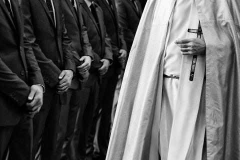 Matt Theilen, un fotógrafo de bodas de California, capturó a este sacerdote en una boda con los padrinos de boda en traje.