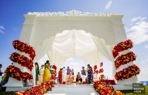 Gujarat wedding photographer captured this photo of an outdoor ceremony taking place on a linen draped platform under a blue sky