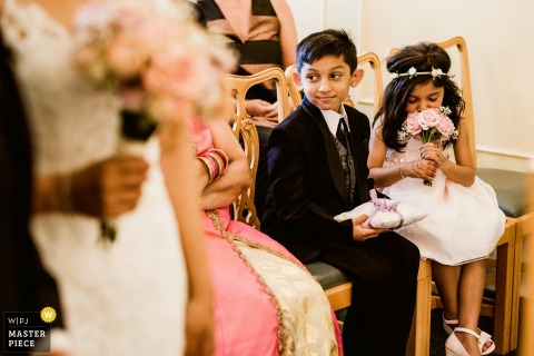 Kent wedding photographer captured this photo of the flower girl sweetly sniffing her bouquet during the ceremony