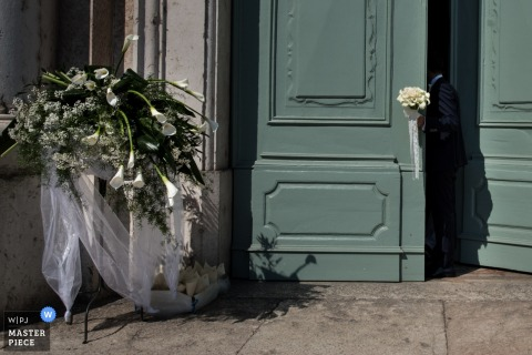 Manuta wedding photographer captured this detail image of a large white floral arrangement that is being displayed in front of a tall teal door