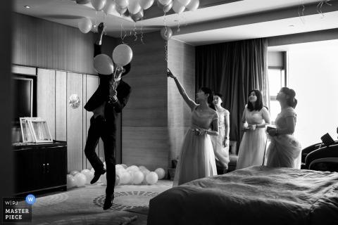Der Hochzeitsfotograf von Fuzhou hat dieses Bild eines Trauzeugen aufgenommen, der von einer Brautjungfer Anweisungen zu einer endgültigen Platzierung des Ballons erhält