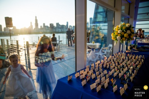 Chicago wedding photographer captured this image of two flower girls looking through a window at the favor table while they wait to enter the reception