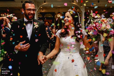 Das Bild der Braut und des Bräutigams, die sich an den Händen halten und lächeln, als Konfetti auf sie regnet, wurde von einem Londoner Hochzeitsfotografen aufgenommen