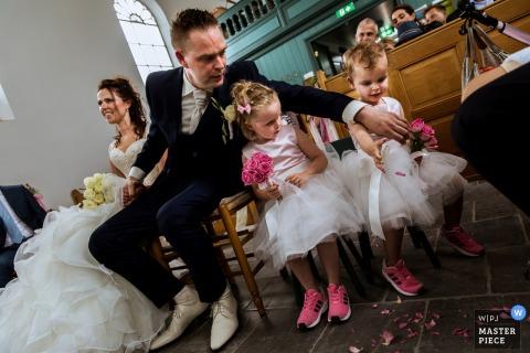 La photographe de mariage de Rotterdam a capturé cette photo de filles en fleurs vêtues de souliers de tennis roses et de robes en mousseline de soie se faisant aider par le marié lorsque des pétales sont renversées sur le sol