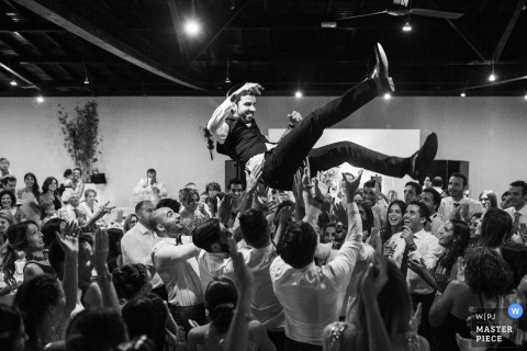 This black and white photo of a groom crowd-surfing was captured by a Braga wedding photographer