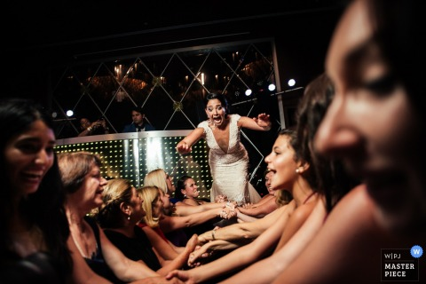 A bride with a slightly terrified look on her face jumps to crowd surf in this funny photo captured by a Madrid wedding photographer