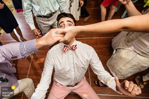 New Jersey wedding photographer caught this wedding guest giving his best shot to an impromptu limbo competition