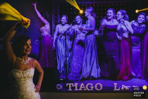 Brazil wedding photographer captured this photo of the bride holding a yellow scarf and dancing in front of a stage of her friends singing karaoke