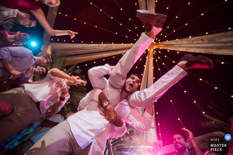 Lima wedding photographer created this image looking up at two guests showing off their dance moves under strings of lights and a night sky