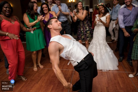 San Diego wedding photographer captured this photo of a groom showing off his dance moves while the bride cheers him on