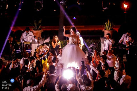 Rome wedding photographer captured this image of the bride being lifted above the dance floor while the band plays live music and wedding guests cheer