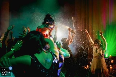 De trouwfotograaf van Londen heeft dit beeld vastgelegd van de bruiloftsgasten die dansen op de verlichte dansvloer terwijl er overal champagne wordt gespoten