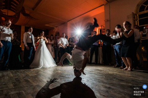 Turin wedding photographer captured this photo of a wedding guest doing a head spin on the dance floor while the others circle and cheer