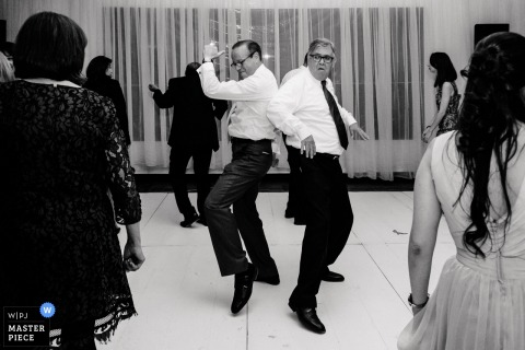 Ecuador wedding photographer captured this black and white photo of the groom and his father showing off their dance moves on the dance floor